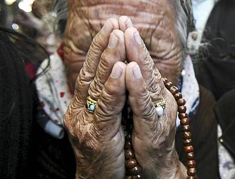Nainen kyynelehtii itsensä sytyttäneen Jamphel Yeshin muistokulkueen aikana. 27-vuotias Yeshi sytytti itsensä tuleen maanantaina kritisoidakseen Kiinan presidentin valtionvierailua Intiassa.