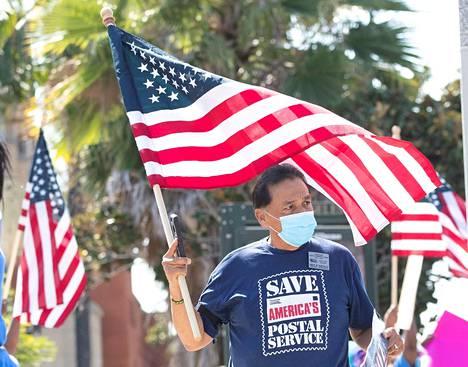 Yhdysvaltain postilaitoksen USPS:n työntekijä osallistui Los Angelesissa mielenosoitukseen jossa vaadittiin viivytysten loppumista, enemmän varoja postille ja laitoksen johtajan Louis DeJoyn erottamista.