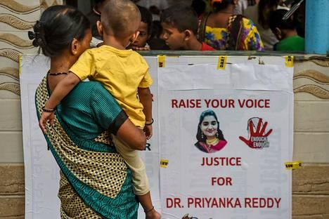 Nainen pysähtyi lapsensa kanssa katsomaan surmansa saaneen eläinlääkärin kuvaa kantanutta julistetta Mumbaissa sunnuntaina järjestetyn rukoustilaisuuden yhteydessä.