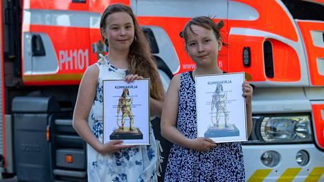 Vilma ja Hertta pääsivät palkitsemistilaisuudessa tutustumaan paloauton toimintaan.