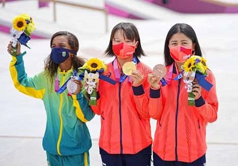 Japanin 13-vuotias Momiji Nishiya (kesk.) voitti kultaa, Brasilian 13-vuotias Rayssa Leal (vas.) hopeaa ja Japanin 16-vuotias Funa Nakayama pronssia rullalautailun naisten katukisassa.