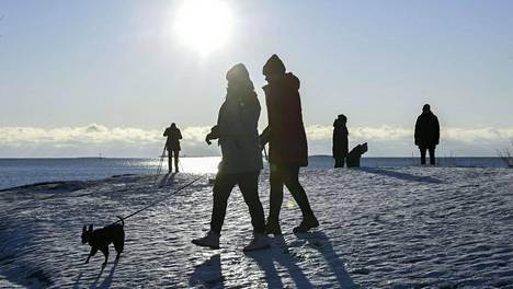 Ulkoilijoita liikkeellä aurinkoisessa pakkassäässä Uunisaaressa Helsingissä 9. tammikuuta 2021.