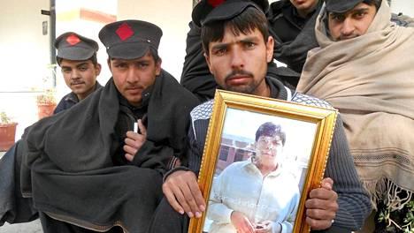 Opiskelija piteli Atizaz Hasanin kuvaa kädessään.