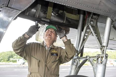 Mekaanikko Pentti Salovaara tarkastaa laskeutumistelineitä ennen lentoa. Hän on huoltanut DC-3-koneita ensimmäisen kerran jo 1960-luvun alussa eli kuutisenkymmentä vuotta sitten.