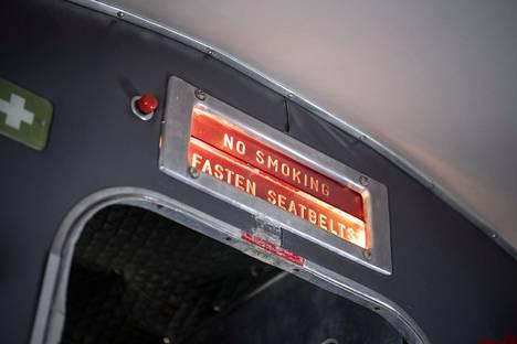 """""""Ei tupakointia"""" ja """"Kiinnittäkää turvavyöt"""", kehottavat viestit matkustamon etuosassa."""