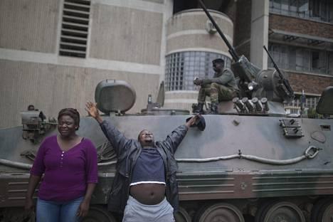 Ihmiset huutavat ja elehtivät mielenosoituksessa sunnuntaina. Mielenosoittajat vaativat presidentti Robert Mugaben eroa.