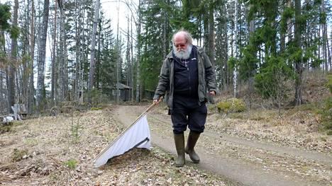Metsäeläintieteen emeritusprofessori Heikki Henttonen ja punkkipyydys. Yksikertaisella kangaspyydyksellä punkkeja voi vähentää mökki- tai kotipihassa, mutta se on vuosien mittainen projekti.