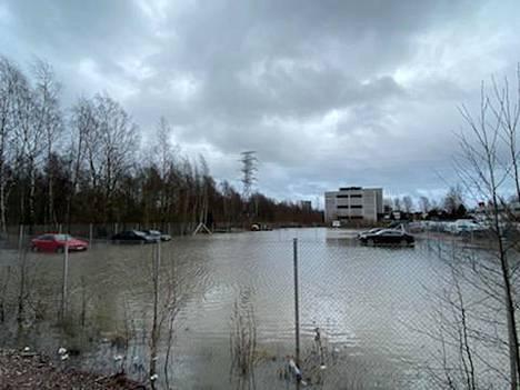Espoon Olarinluoma lainehtii, tie on suljettu ja parkkipaikka veden vallassa.