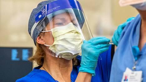 Hoitaja antamassa Pfizerin rokotetta sairaalassa Norwichissa Yhdysvalloissa.
