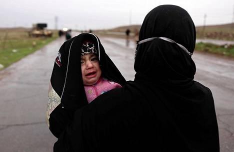 Kotinsa jättäneet nainen ja lapsi kuvattiin pakomatkalla sateessa.