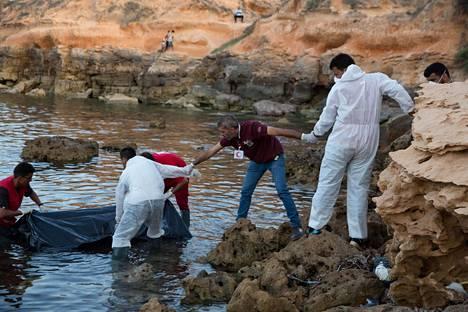 Libyan Punaisen puolikuun työntekijät nostavat hukkuneita siirtolaisia Tajouran rannikkoalueella kesäkuussa 2017.