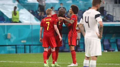 Huuhkajien Joona Toivio seuraa pettyneenä, kun Belgian pelaajat juhlivat 2–0-maalia.