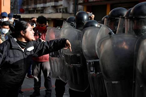 Nainen kertoi mielenosoituksen yhteydessä mielipiteensä mellakkapoliiseille.