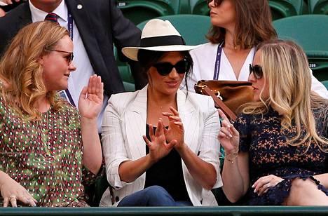 """Meghan ystävineen istui ns. """"tavisten"""" keskellä Wimbledonissa. The Times uutisoi tuolloin herttuattaren aiheuttaneen vaatimuksillaan harmaita hiuksia järjestäjille."""