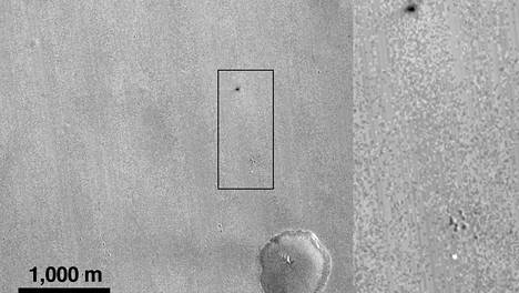 NASAn ottamissa kuvissa uskotaan näkyvän Mars-laskeutujan laskuvarjo (vaalea läikkä alhaalla) sekä itse laskeutuja (tummempi piste ylhäällä).