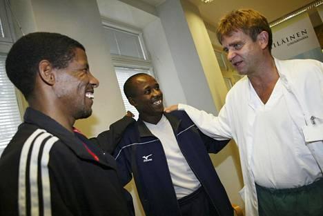 Aki Hintsa olympiavoittajien Haile Gerbreselassien (vas.) ja Abera Gezahegnen kanssa vuonna 2004.