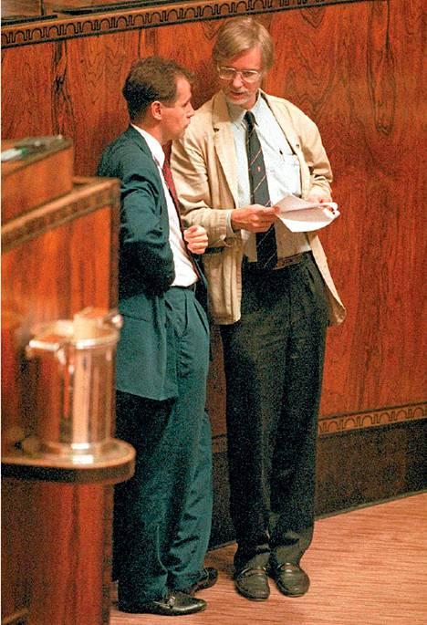 Sdp:n kansanedustaja Jouni Backman keskustelee puoluetoverinsa Erkki Tuomiojan kanssa eduskunnassa 8.10.1993.