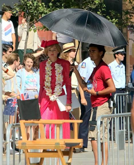 Emma Corrin Lady Di:nä pinkissä asussaan The Crown -sarjan kuvauspaikalla.