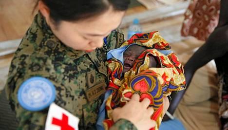 Eteläkorealainen YK-sotilas hoitaa vauvaa Borin pakolaisleirissä.