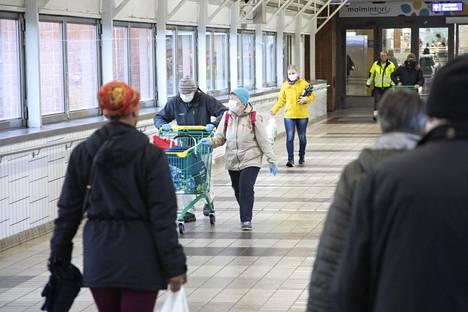 Kasvomaskeihin sonnustautuneita ihmisiä kauppakeskus Novassa Helsingin Malmilla.