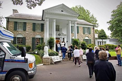 Elviksen kotitalo Graceland vetää yhä kävijöitä jonoksi asti. Yläkuvassa Elvis ja yksi hänen autoistaan Gracelandin edustalla maaliskuussa 1965.