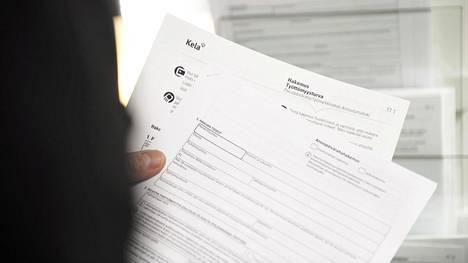 Työtön tutustuu työttömyysturva hakupaperiin TE-palvelun tiloissa Helsingissä.