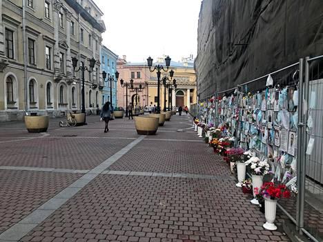 Koronaan kuolleiden lääkäreiden ja hoitajien kuvat katselevat muistoaidalta suoraan kohti Pietarin terveyskomitean toimistoa.