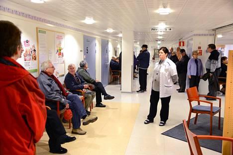 Influenssarokotusten annettiin terveyskeskuksessa vuonna 2014 näin. Koronaturvallisuus ei salli pitkiä jonoja sisätiloissa.