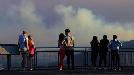 Ihmiset katsovat maastopaloista nousevaa savua Uudessa Etelä-Walesissa 6. joulukuuta 2019.