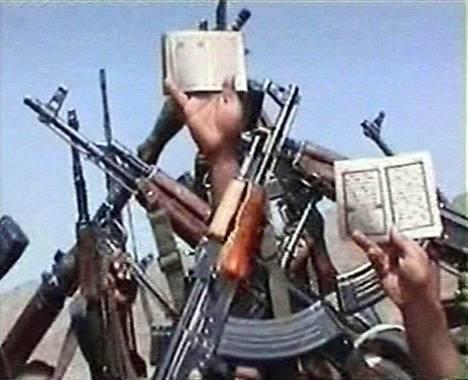 Videolta kaapatussa kuvassa Osama bin Ladenin taakseen saamat islamistit esittelevät aseitaan ja Koraanin sivuja.