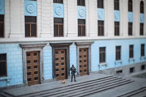 """Muovinen """"kohtelias mies"""" seisoo Krimin hallintorakennusta esittävän pienoismallin edessä. Krimin pienoismallimuseo sijaitsee Bahtshisaraissa Krimillä."""