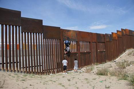 Nuoret miehet kiipesivät Yhdysvaltain ja Meksikon rajalla sijaitsevan aidan yli Ciudad Juarezissa perjantaina.