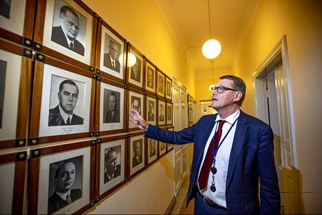Valtiovarainministeri Matti Vanhanen Valtioneuvoston linnassa. Vanhanen tutkii entisten valtiovarainministerien kuvia käytävällä. Vanhanen kertoo tavanneensa muuan muassa V. J. Sukselaisen, joka toimi valtiovarainministerinä 1950–1951 ja 1954.