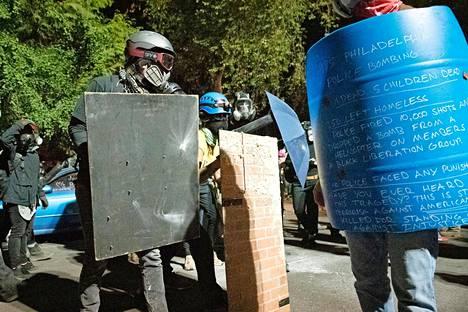 Mielenosoittajat suojautuivat erilaisin kilvin poliisien ammuttavilta pippurisumutteilta.