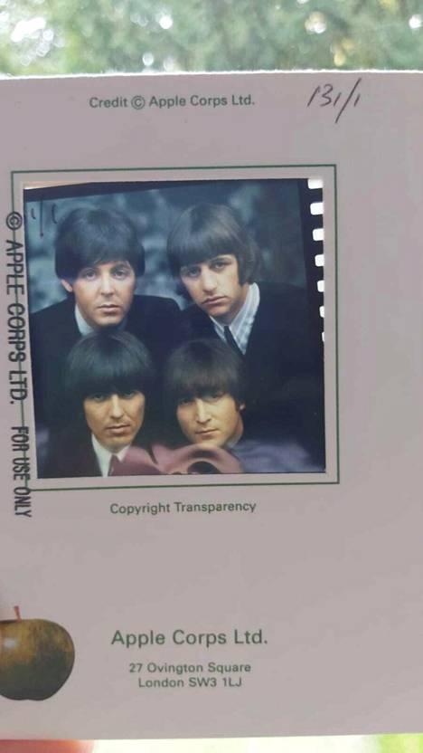 Kuvia myyvän pariskunnan kuva pahvikehyksissä olevasta Beatles-diasta. Mukana Apple Corpsin leima omenoineen.