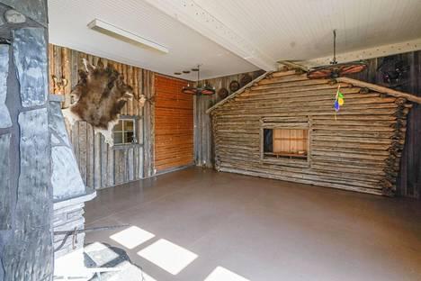 Tuula Koivuniemi on sisustanut koulurakennuksen omintakeisella tyylillä. Olohuonetta koristaa suuri takka sekä vanhan ladon seinä.