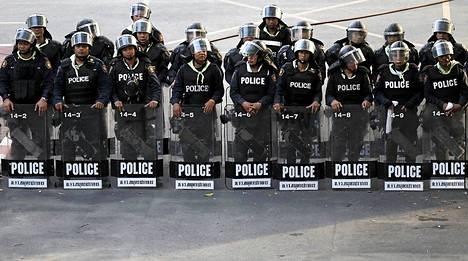 Kuva torstailta, jolloin poliisit suojasivat pääministeri Yingluck Shinawatraa, kun hän puhui mielenosoittajille Bangkokissa.