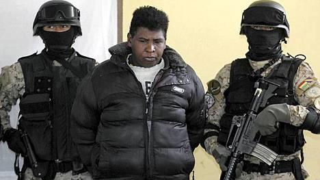 Naamioituneet poliisit saattelevat murhabussijengin johtajaksi epäiltyä Julio Edwin Valdezia.