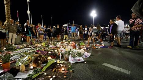 Ihmisiä tuomassa kukkia ja esineitä iskun uhrien muistolle Promenade de Anglaisilla Nizzassa 16. heinäkuuta.