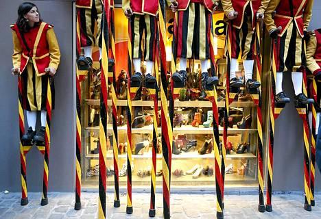 Puujaloilla kävelevät akrobaatit lepäävät kenkäkaupan vieressä kesken kansanperinnefestivaalien Brysselissä.