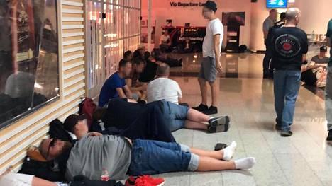 Virolaisia kanssamatkustajia lepäämässä lähtöaulan lattialla.