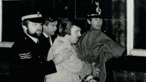 Poliisit taluttavat Peter Sutcliffeä oikeuden kuultavaksi 1. toukokuuta 1981 Bradfordissa Yorkshiressa.