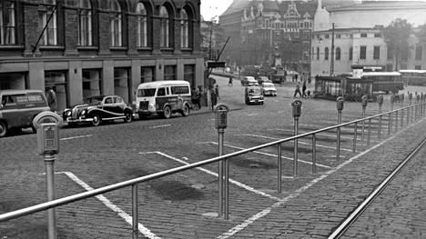 Aamu Helsingin Erottajanmäellä 27. 9. 1961 yllätti keskusta-autoilijat: mukulakivirinteeseen oli ilmestynyt peräti 55 maksullista pysäköintipaikkaa. Saapa nähdä, minkä ruudun tuo lähestyvä Volvo Duett mahtaakaan valita.
