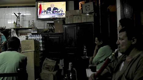 Miehet kuuntelivat presidenttiehdokas Ahmed Shafikin puhetta Kairossa.