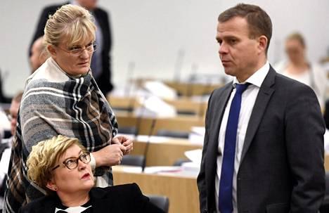 Keskustan kunta- ja uudistusministeri Anu Vehviläinen (alhaalla), perussuomalaisten sosiaali- ja terveysministeri Pirkko Mattila ja kokoomuksen valtiovarainministeri Petteri Orpo (oik.) eduskunnan täysistunnossa 23. syyskuuta.