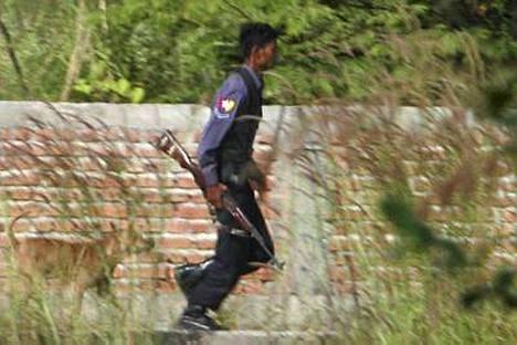 Burmalainen poliisi juoksee karensissien kanssa käydyn tulitaistelun aikana maanantaina.