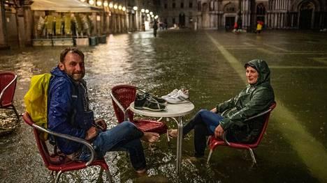 Torinosta Venetsiaan torstaina saapunut turistipariskunta jaksoi hymyillä Pyhän Markuksen torin terassilla istuessaan, sääolosuhteista huolimatta.
