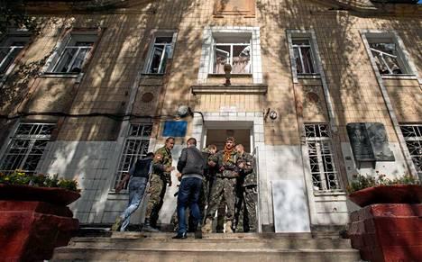Venäläismieliset kapinalliset partioivat donetskilaiskoululla sen jälkeen, kun kranaattituli tappoi kymmenen ihmistä koululla ja sen läheisellä kadulla.