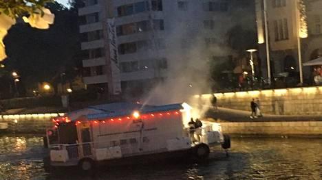 Henkilökunta tyhjensi illalla savuavan Aura-jokilautan Turussa.