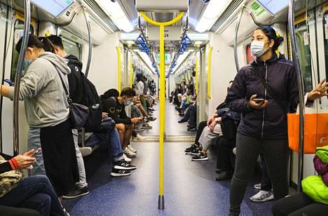 Matkustajat käyttivät hengityssuojaimia matkustaessaan metrolla Hongkongissa.